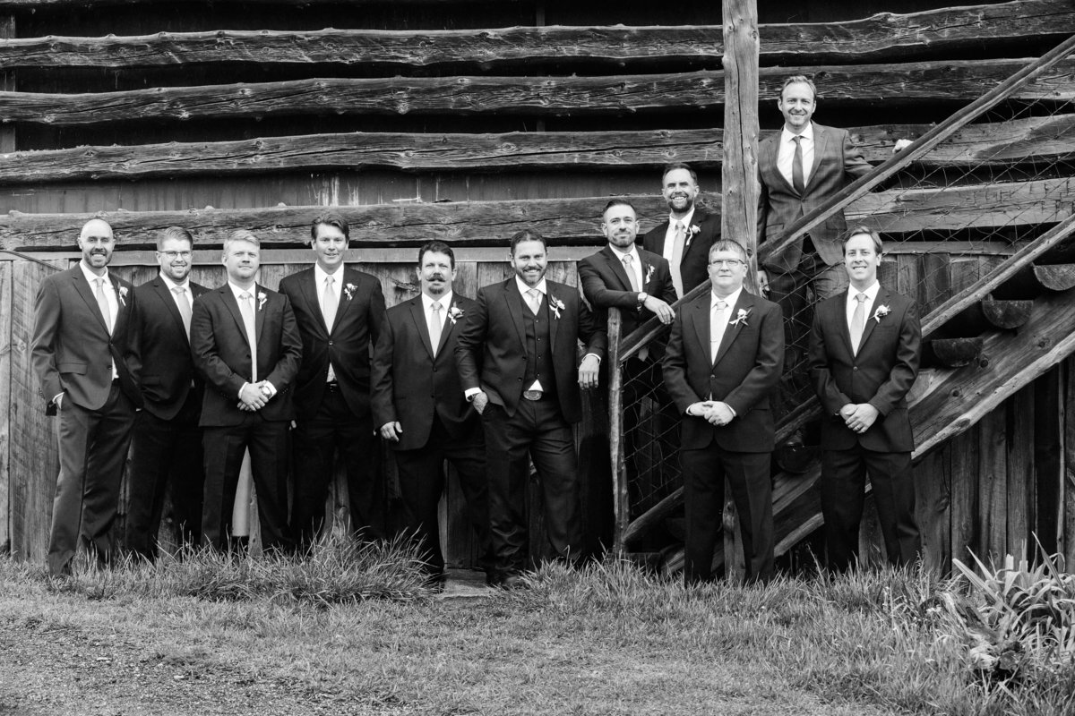 A group of groomsmen in front of a barn standing together.