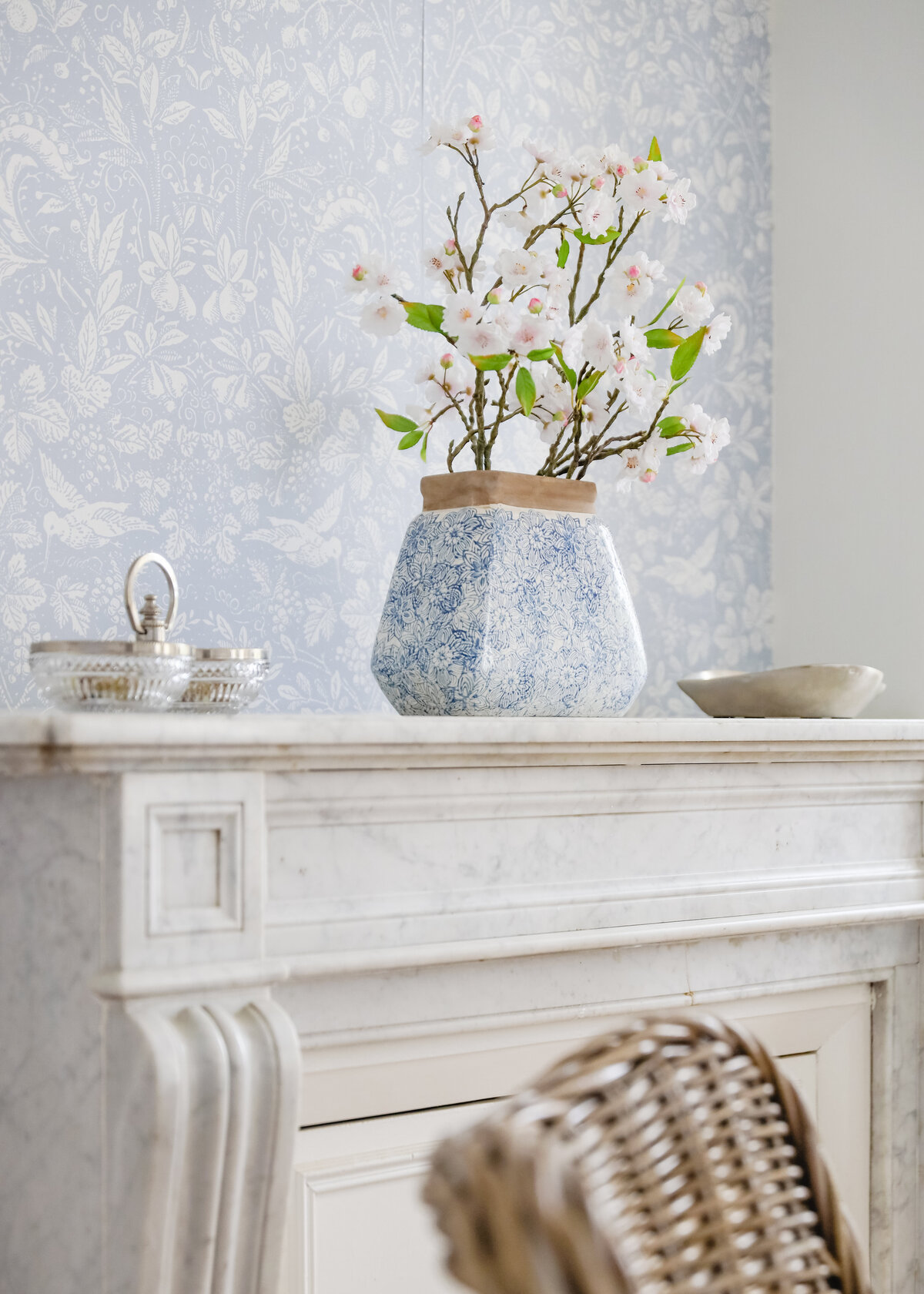 A patterned powder blue wall paper is behind a blue vase on a marble fireplace.