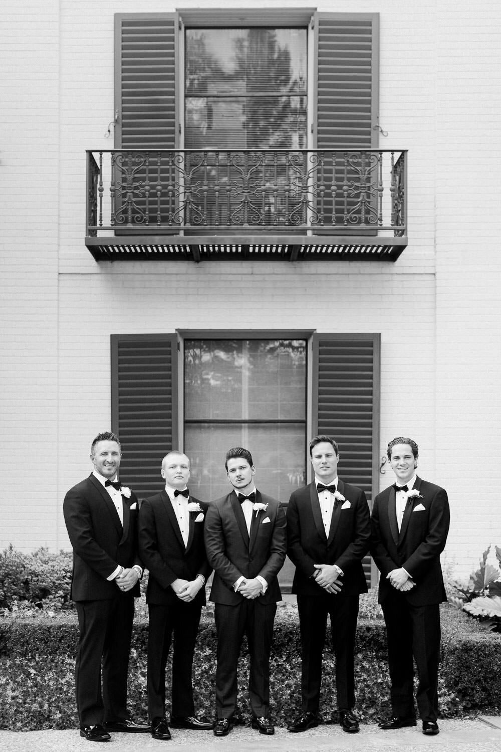 groom and four groomsmen in tuxedos standing in a row in front of white house