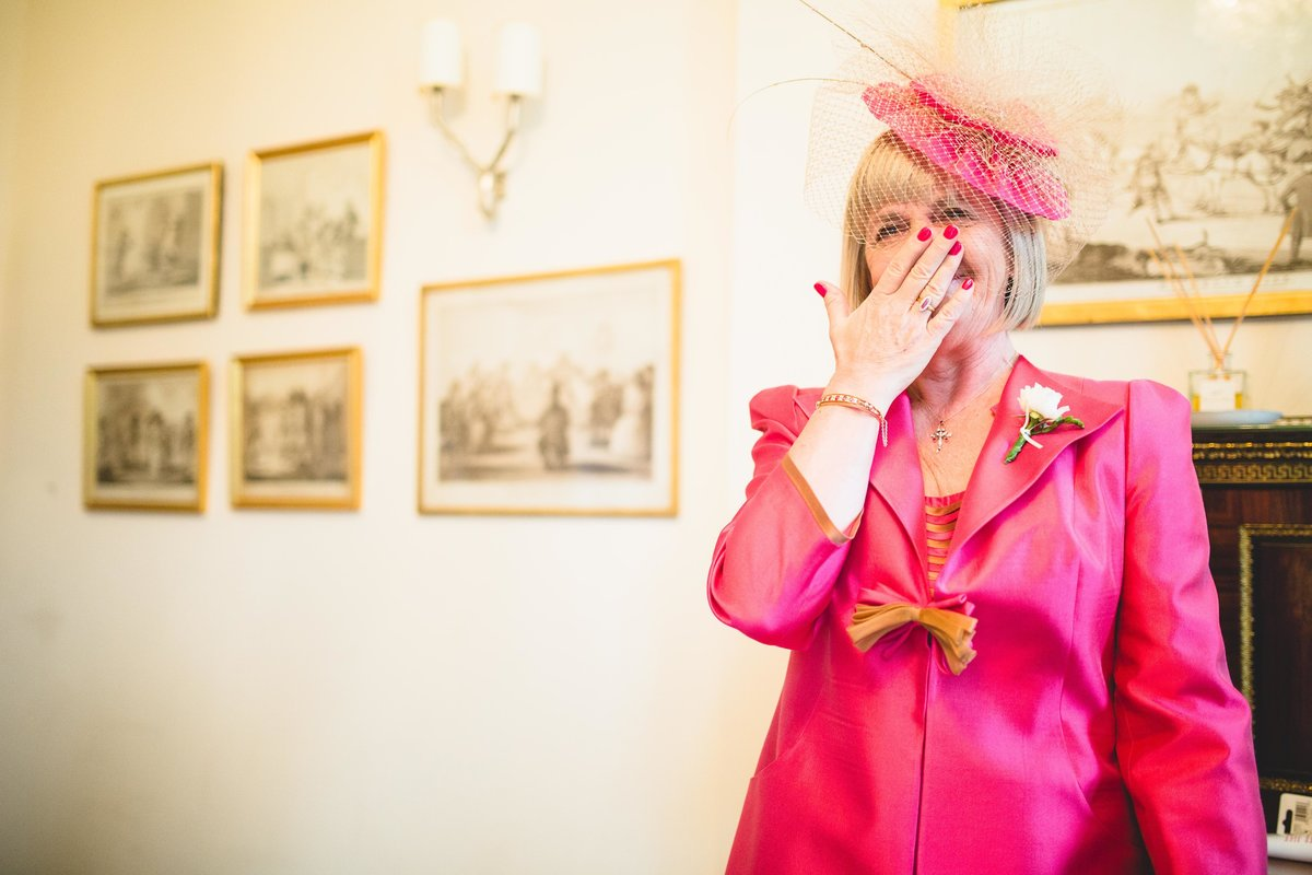 mother of the bride crying when she sees her daughter. wearing pink outfit and fascinator at iscoyd park