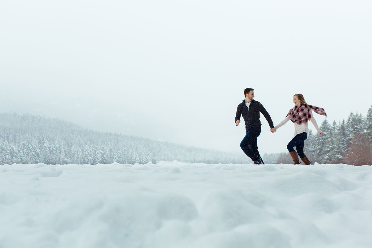 Photo of couple running in the snow