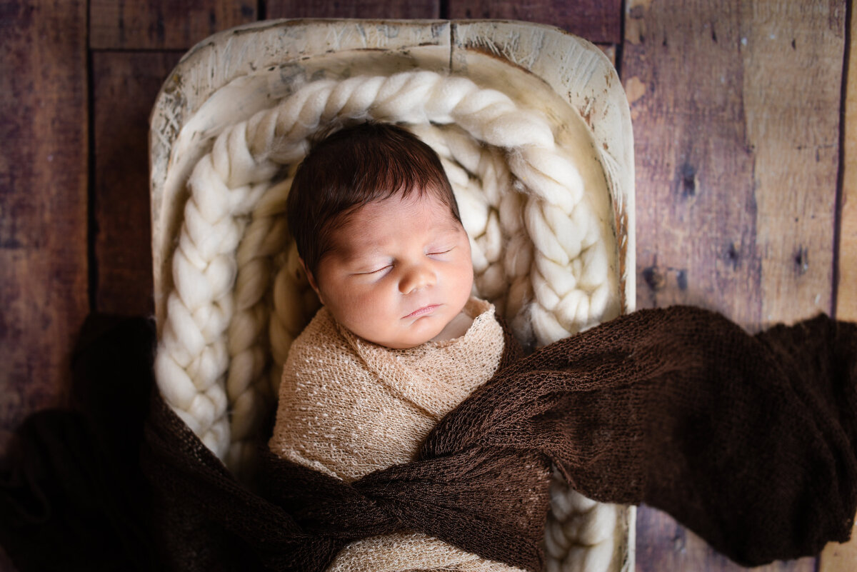 Beautiful Mississippi newborn photography: Boy wrapped in ivory with head of dark hair sleeps in dough bowl on wood floor