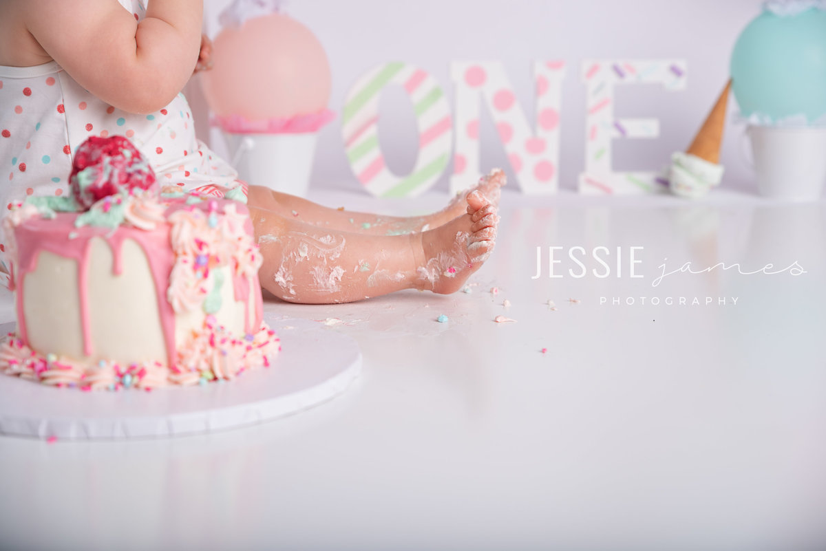 closeup of baby girls feet covered in cake