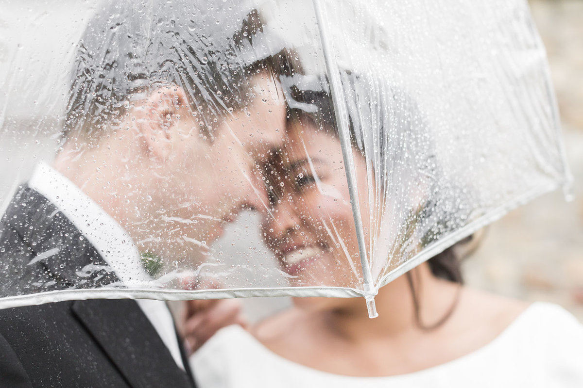 man and woman kissing under umbrella