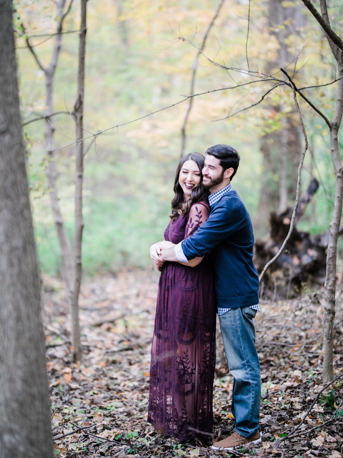 Couple hugging by the woods