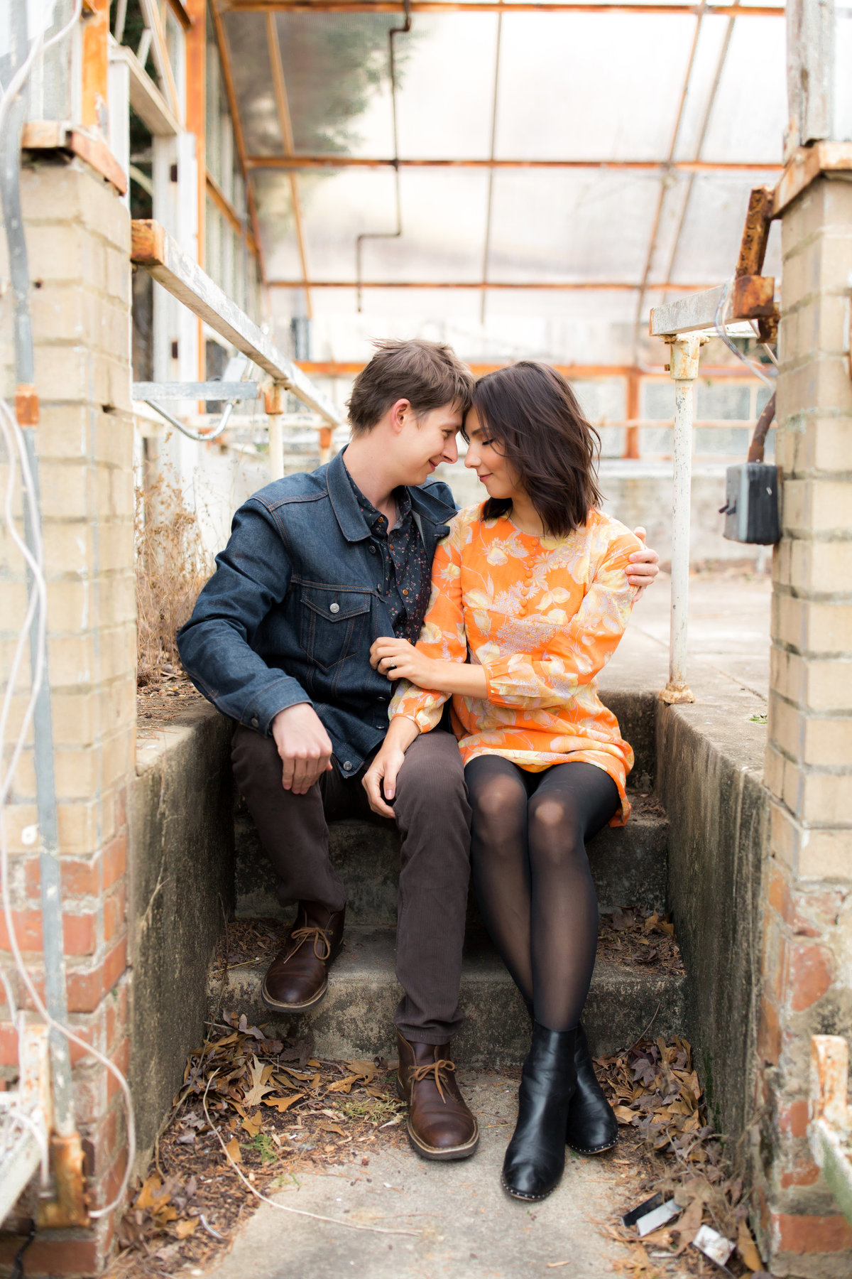 photographer takes picture of trendy engaged couple at Briarcliff mansion greenhouse in Atlanta