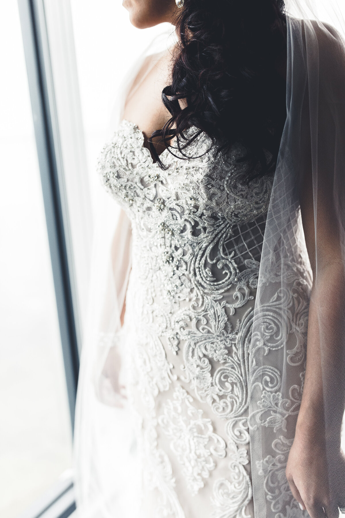 bride by window in lace dress moody photography