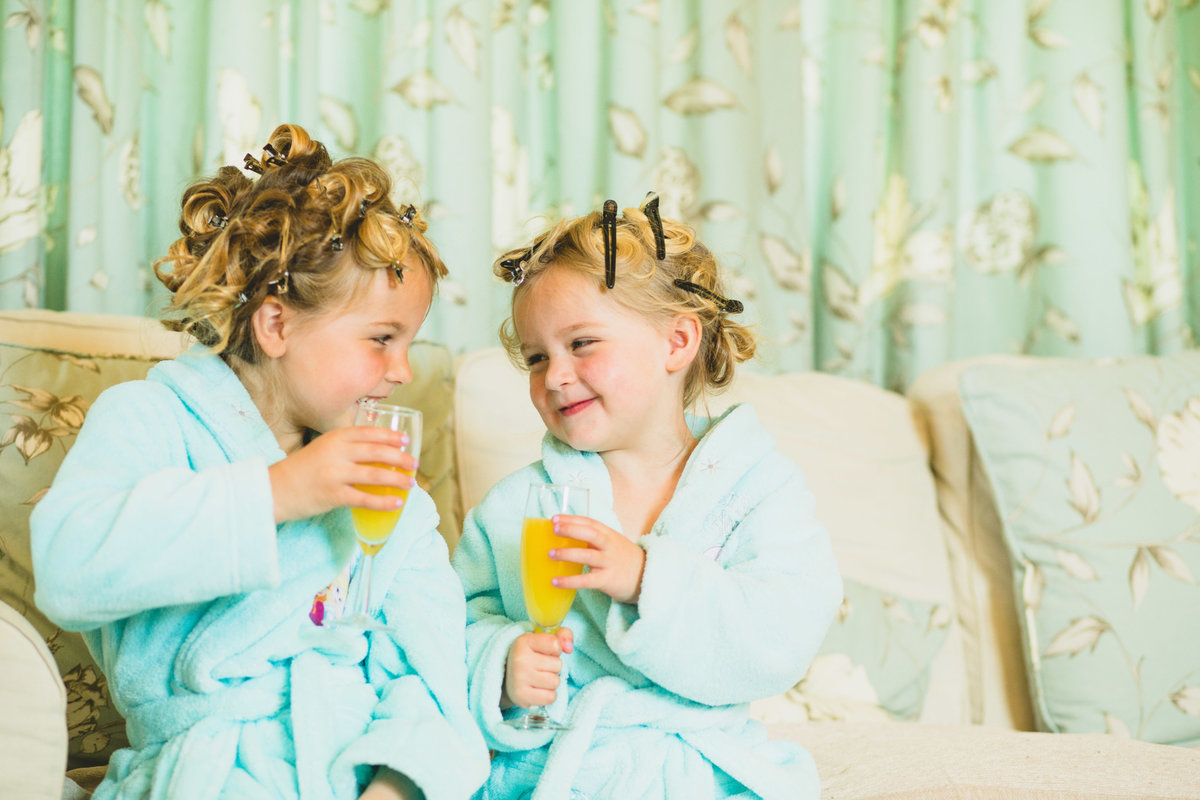 2 flower girls drinking from champagne glasses