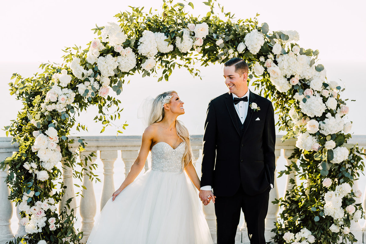 Floral half moon arch with bride & groom