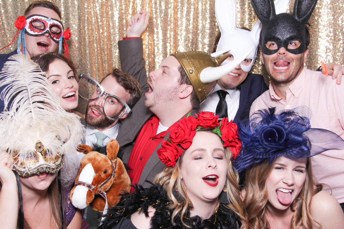 group of friends with props posing to the photo booth