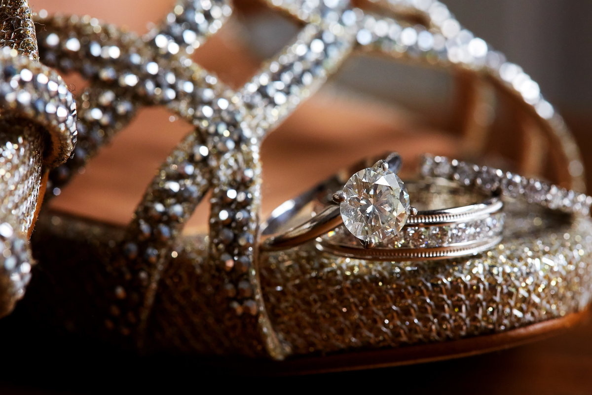 Diamond engagement ring and diamond and gold wedding bands sitting atop beaded bridal shoe in Charleston, SC