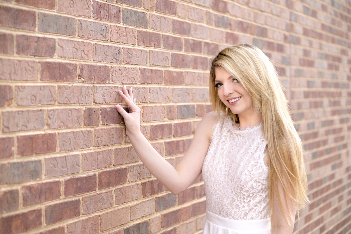 Girl in white dress with long beautiful blonde hair stands next to a brick wall