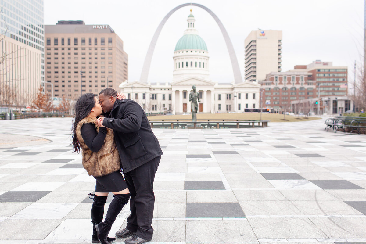 Winter Engagement  Session with black dress fur vest and boots couple kissing in front of The St. Louis Arch  at Kiener Plaza in St. Louis by Amy Britton Photography Photographer in St. Louis