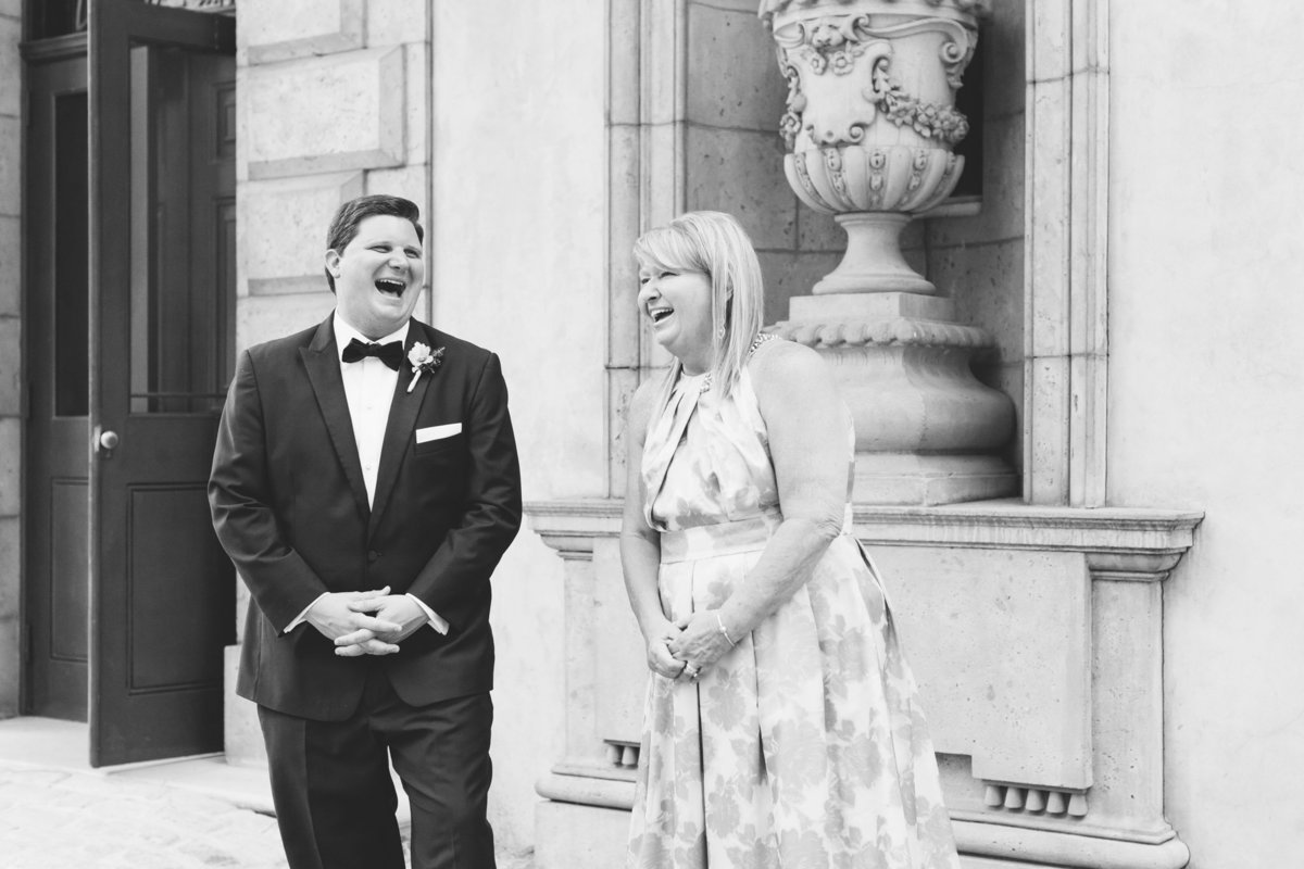 The groom and his mother share a laugh during family portraits. Photo by luxury destination wedding photographer Rebecca Cerasani.