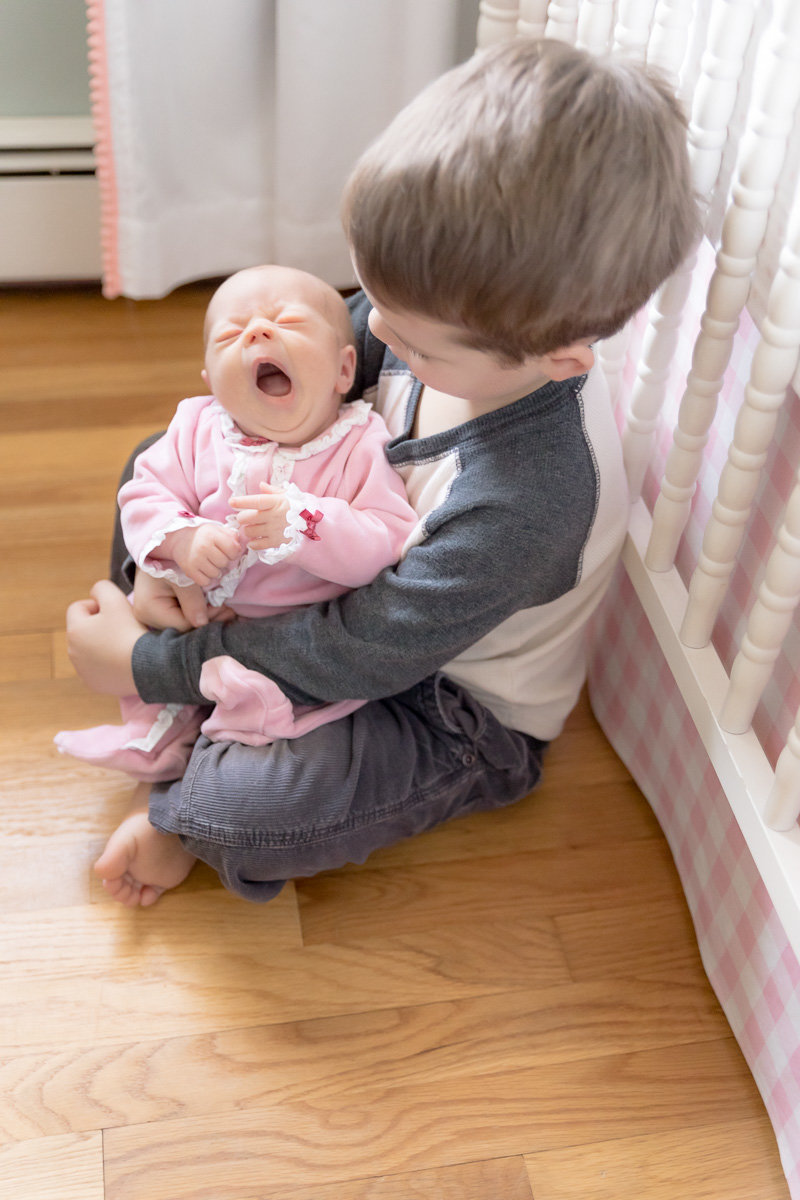 Big brother holds a yawning newborn sister