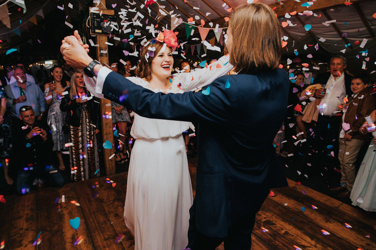 Couple surprised by confetti canon during first dance