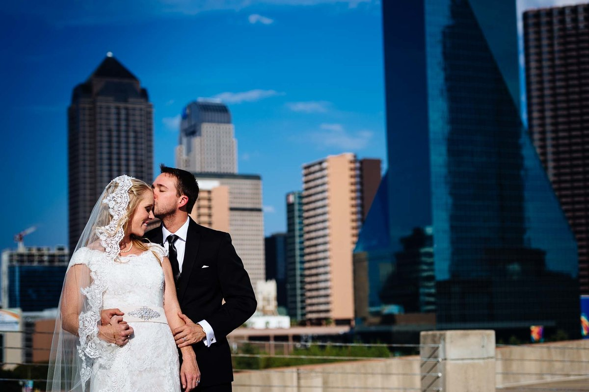 portrait of bride and groom in front of dallas skyline