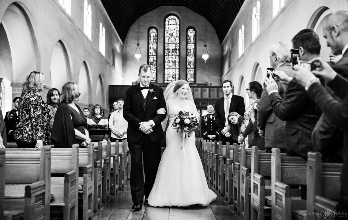 Beautiful B&W photo of bride walking down aisle at Shove Chapel in Colorado Springs