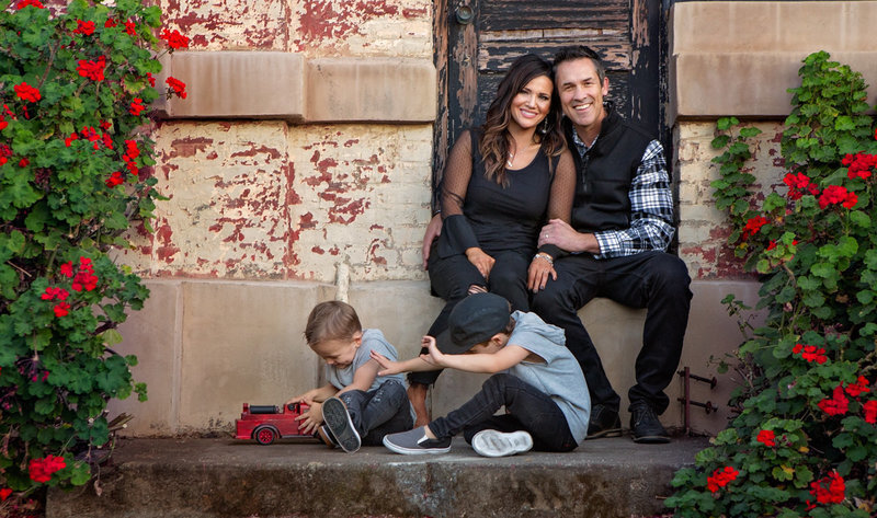 Sky 9 Studio | Professional photo of family with two boys playing with fire truck toy outside of brick building with black, grey, tones against brick wall with border of red flowers
