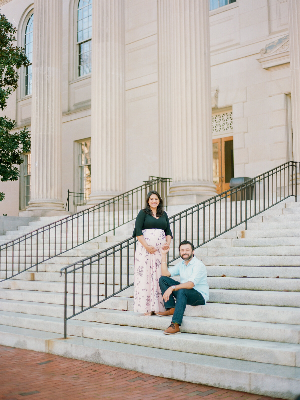 Husband and wife pose on steps during maternity portrait session