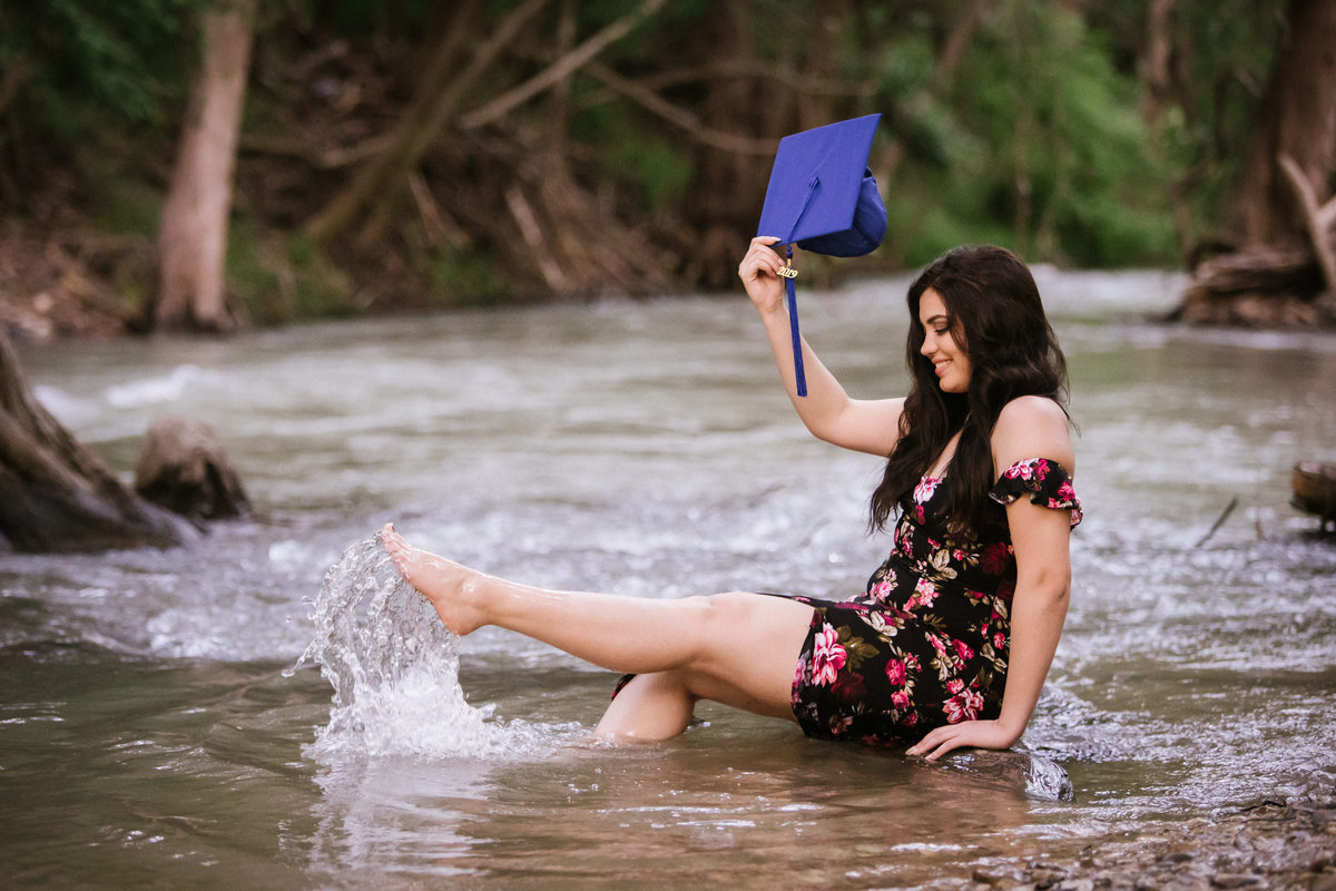 high school senior girl kicking her feet in river water by San Antonio senior photographer