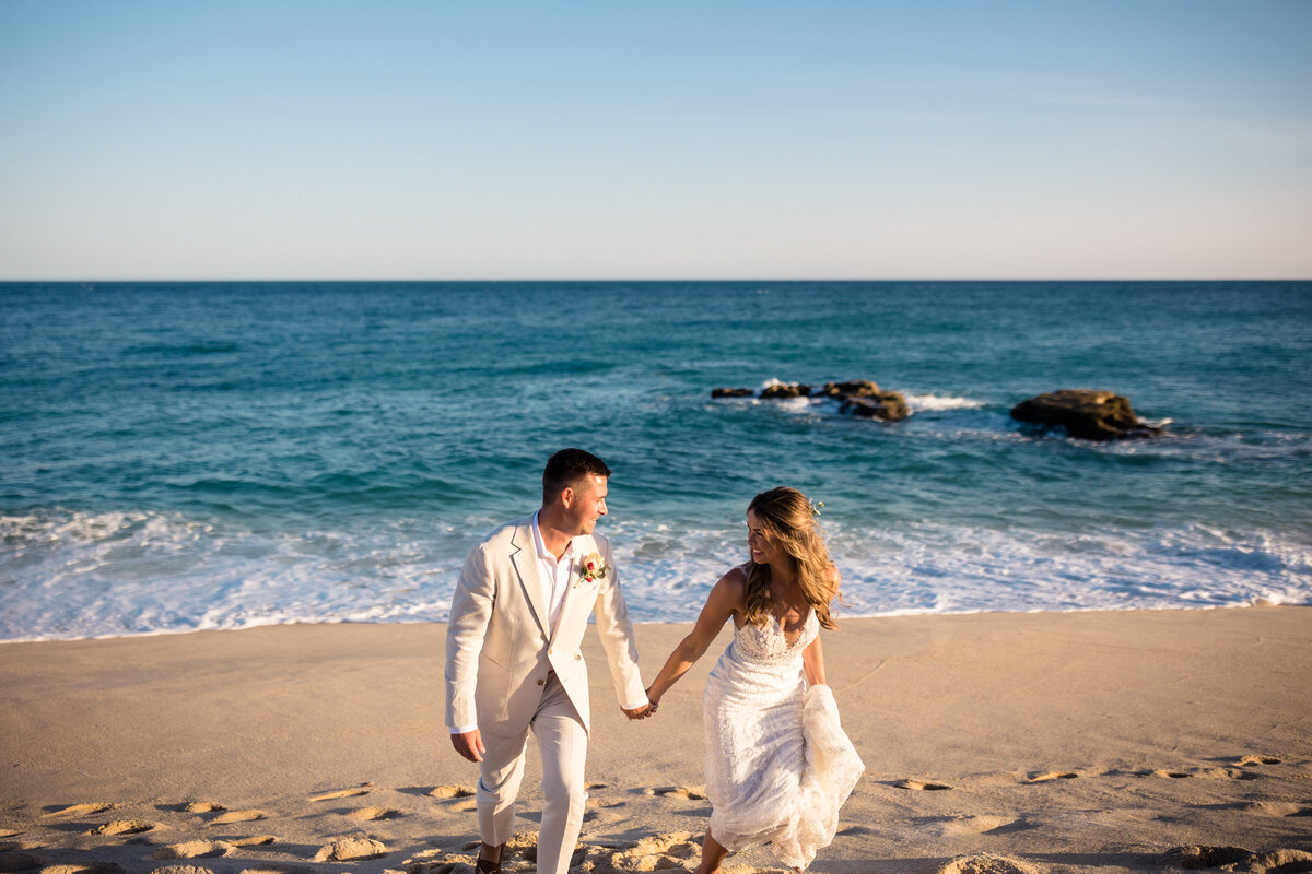 bride and groom walking on beach in cabo