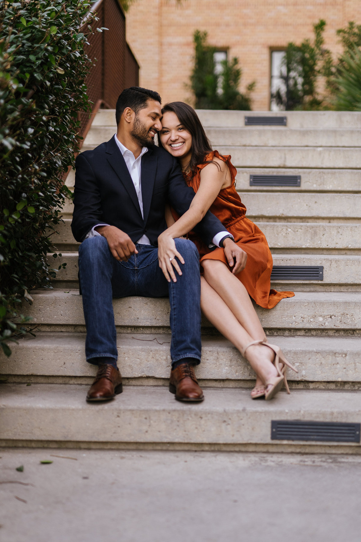 Fiancé staring at his fiancée sitting on steps at the Historic pearl while on their engagement session by Expose The Heart.