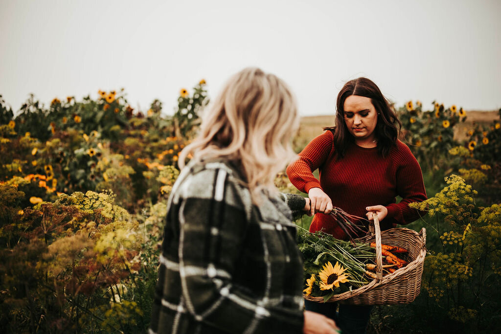 two women standing in a garden putting veggies in a basket