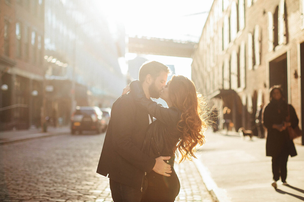 Couple kissing on NYC street sunset