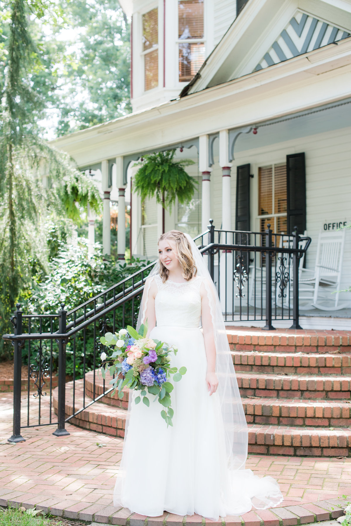 A bride with a lace topped dress and a cathedral length veil holding onto a colorful wedding bouquet looking off to the side in front of the Gardens at Gray Gables