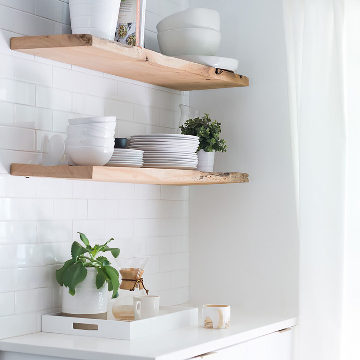 Wooden kitchen shelves with dishware, cookbooks, and plants in all natural, warm kitchen