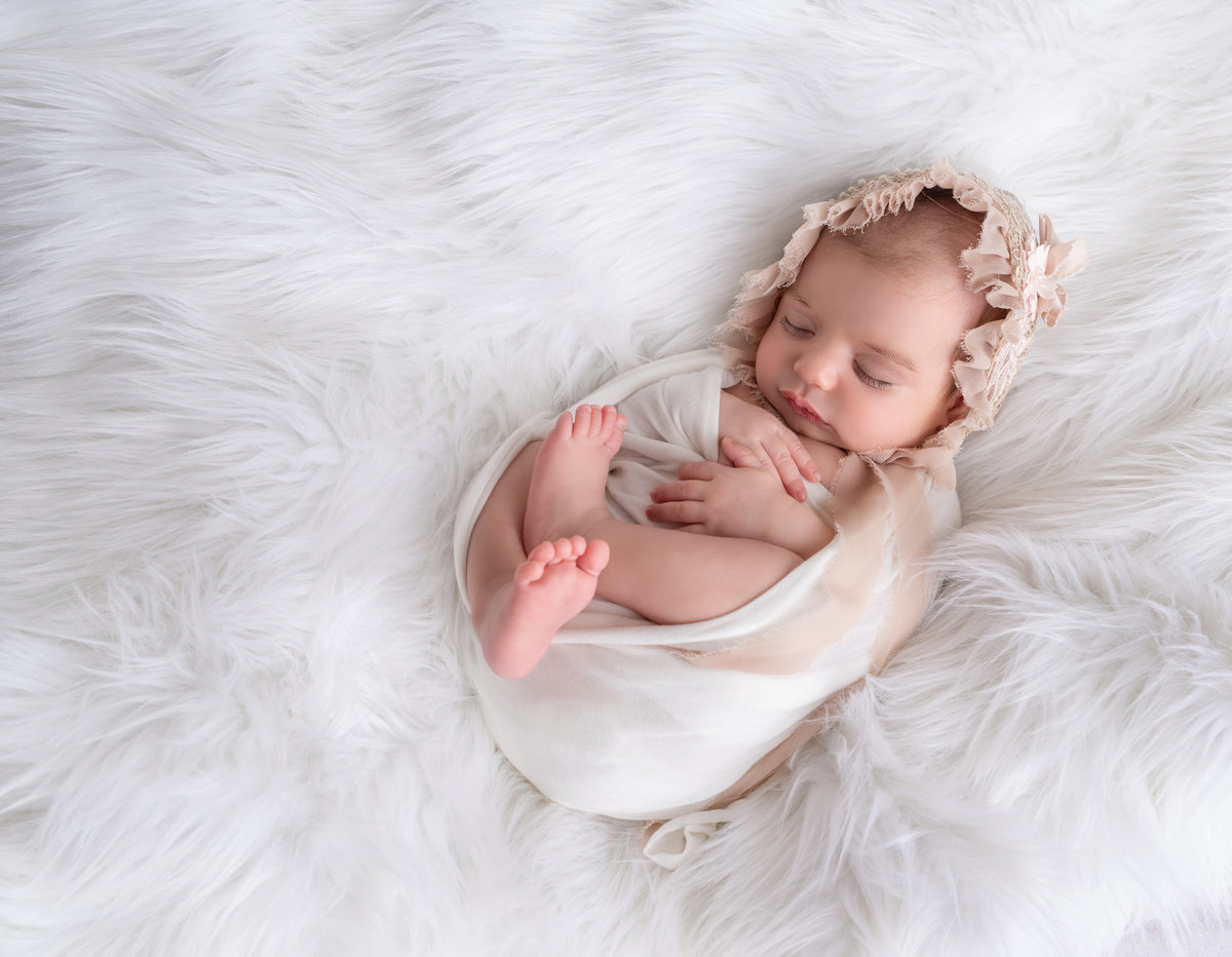 newborn girl on a white fur blanket