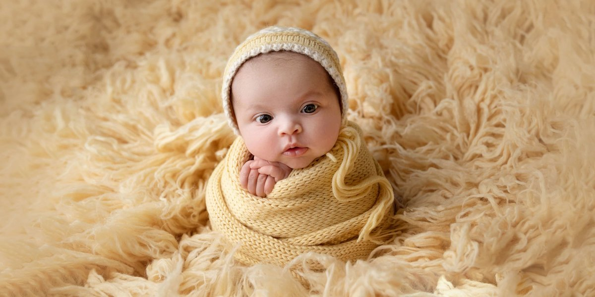 Little girl in a yellow newborn photography setup