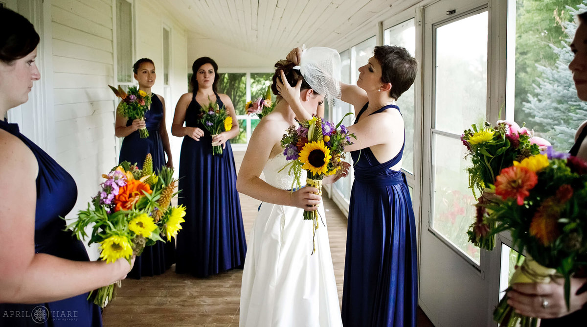 Bridesmaids wearing blue help bride with her birdcage veil on the screen in porch at Chatfield Farms in Colorado