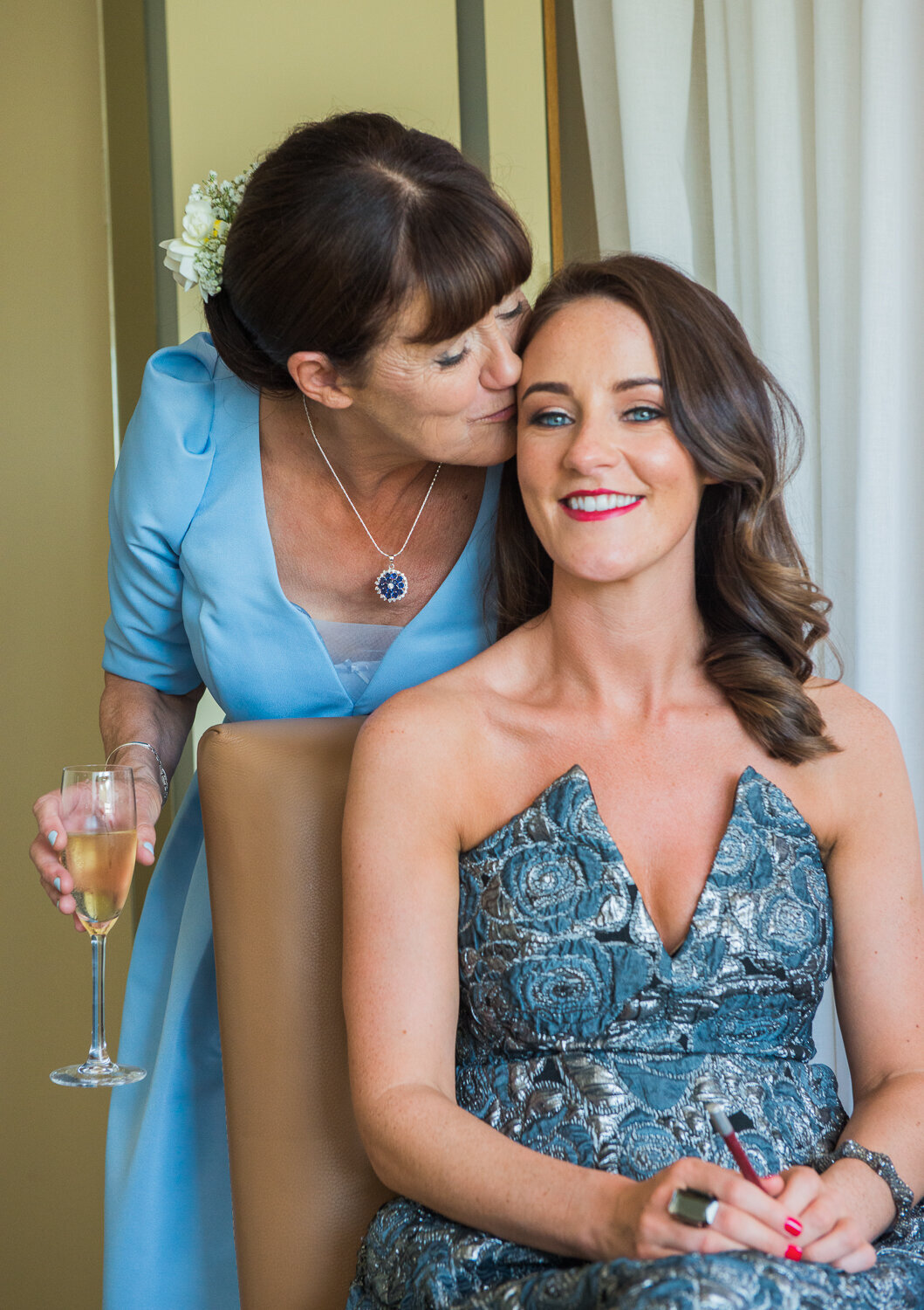 Mum kissing daughter at wedding preparations