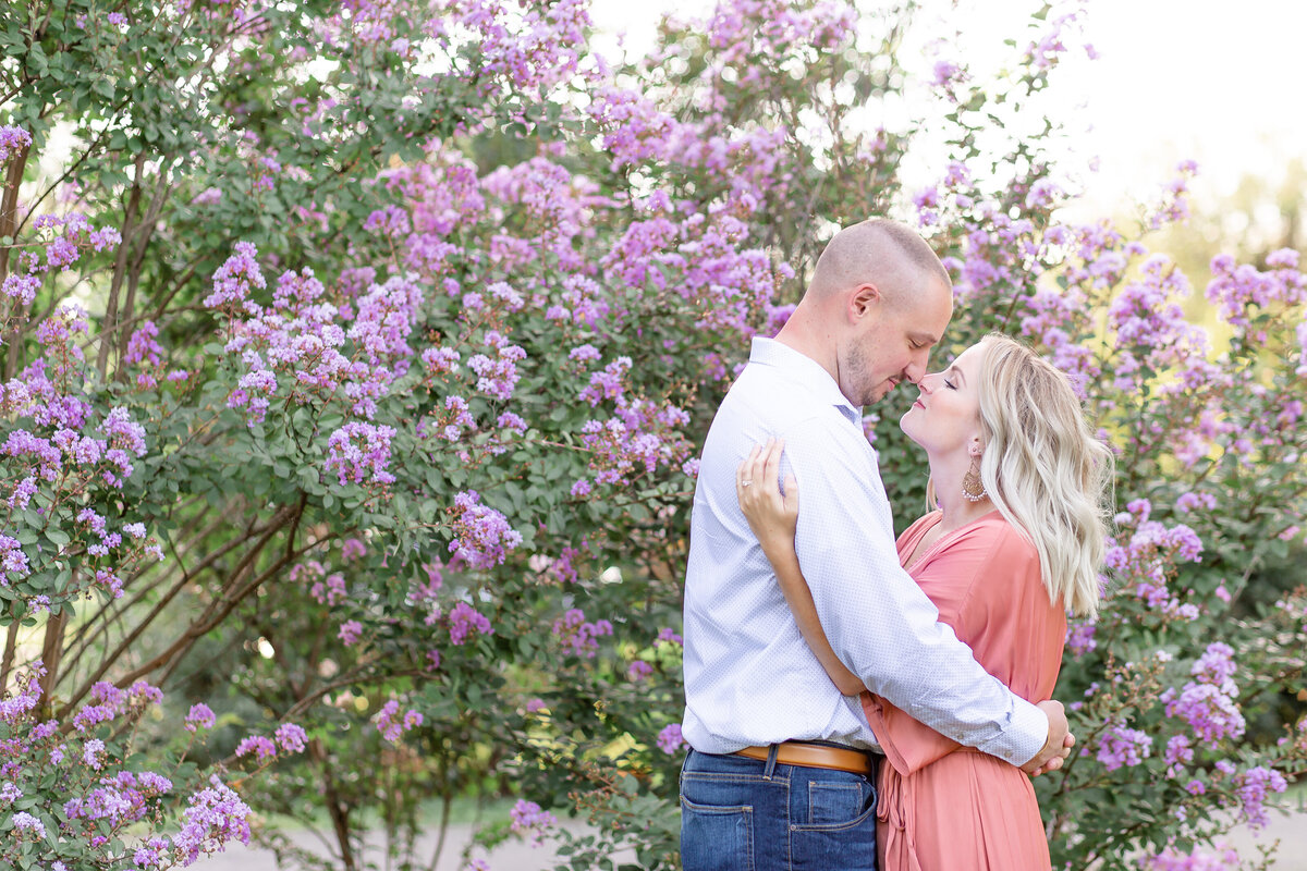 Summer Sunset Engagement Session with pink maxi dress couple  by purple flowers  at Tower Grove Park in St. Louis by Amy Britton Photography Photographer in St. Louis