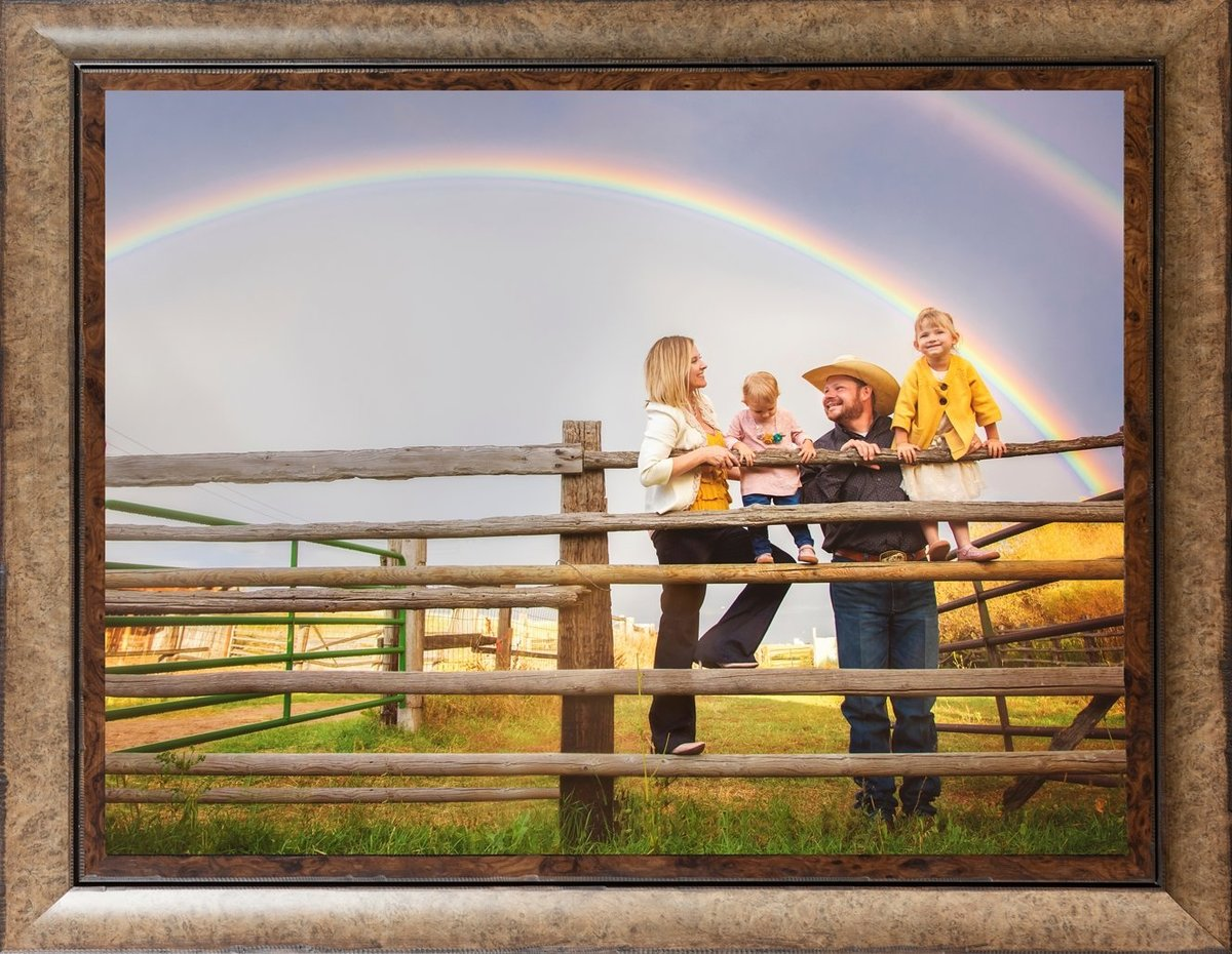 Family with two small girls standing by a fence looking at a rainbow in Cheyenne Wyoming.