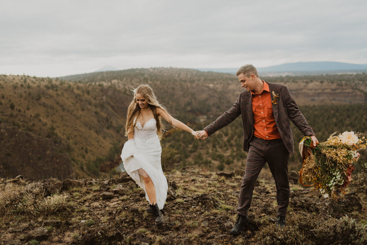 bride and groom on mountain top with bouquet