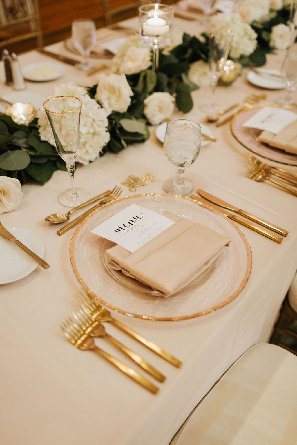 romantic tablescape with gold silverware and gold rim charger