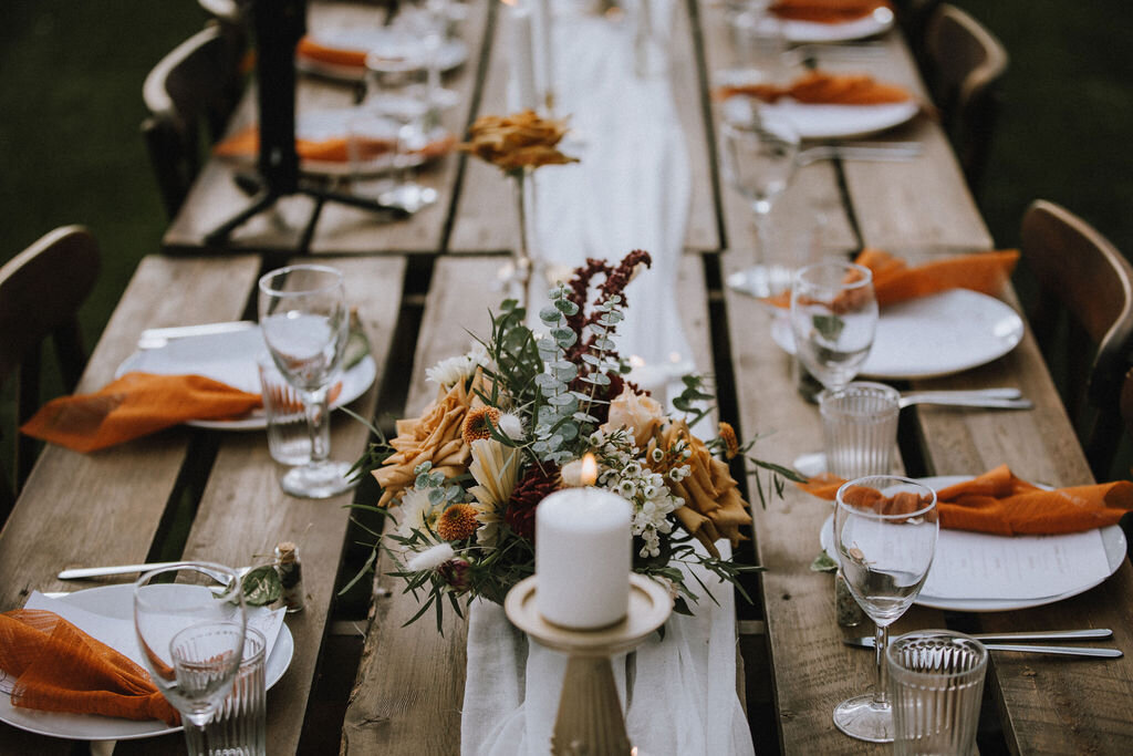 wedding  wood tables and chairs with white plates, orange napkins, candles and flowers