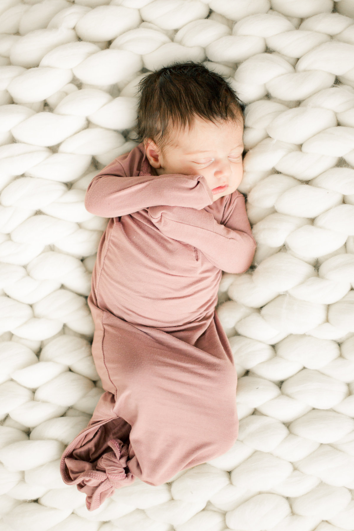 baby lays on chunky white wool blanket for newborn portraits