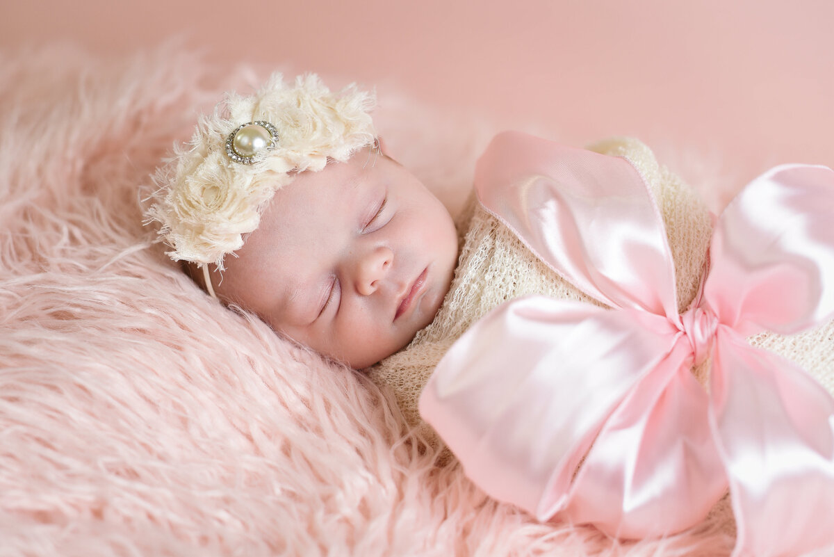 Beautiful Mississippi newborn photography: newborn girl red wrapped with a pink gift ribbon, Mississippi Newborn Photographer
