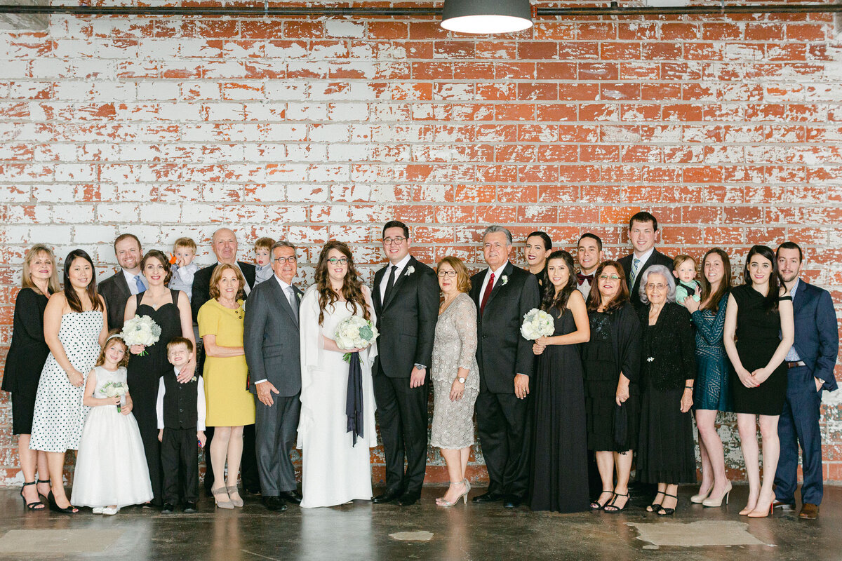 Intimate Houston Wedding day family group shot against brick wall