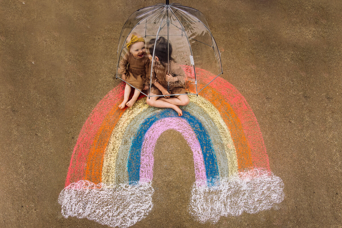 kids under umbrella on a chalk colored rainbow