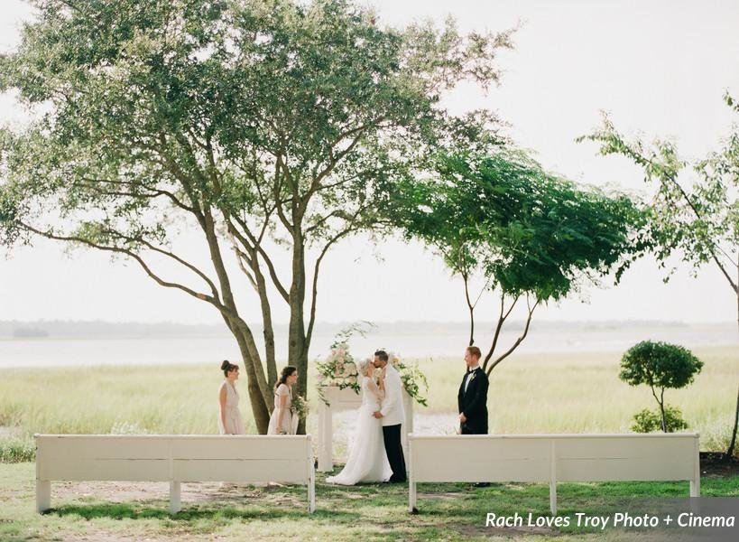 A wedding in front of the marsh with vintage church pews.