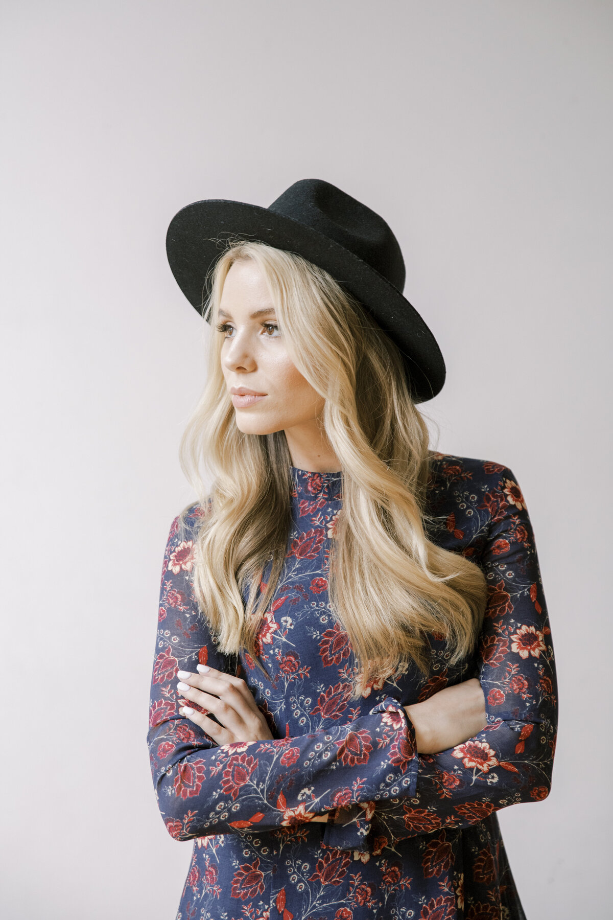blond woman with black hat and floral top crossing her arms in front of her and looking off into the distance