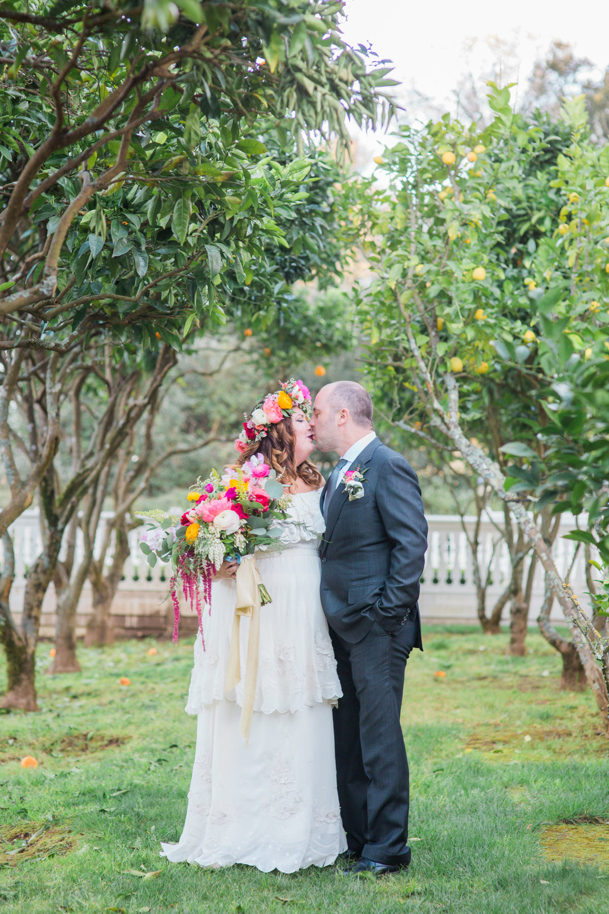 Bride and groom kissing under grove of trees Bride and groom joining cocktail hour at Madrona Manor in Healdsburg California.jpg