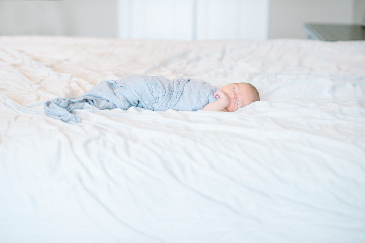 baby in light blue swaddle sleeping on white bed