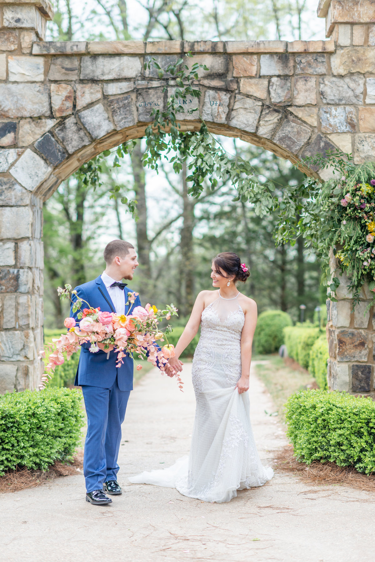 Man in blue suit holds a colorful bouquet while guiding a brunette bride through a large stone arch in a garden