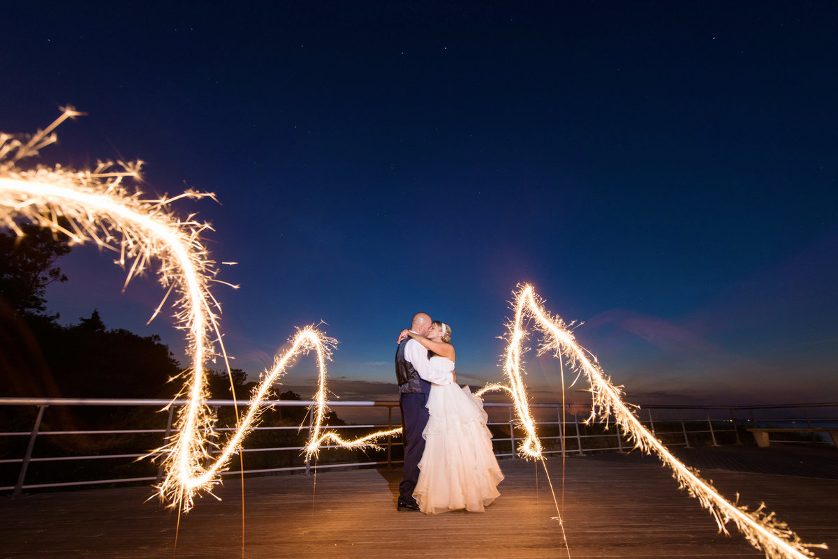 sparklers night shot of bride and groom on the boardwalk at Pavilion at Sunken Meadow wedding